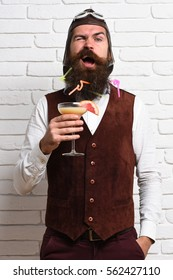 handsome bearded aviator man with long beard and mustache on funny face holding glass of alcoholic cocktail in vintage suede leather waistcoat with hat and glasses on white brick wall background