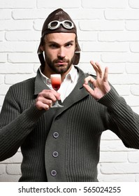 handsome bearded aviator man with long beard on serious face holding glass of alcoholic shot in gray knitted sweater with hat and glasses on white brick wall background