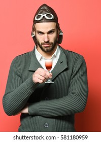 handsome bearded aviator man with long beard on serious face holding glass of alcoholic shot in gray knitted sweater with hat and glasses on red studio background