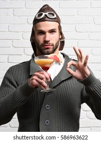 handsome bearded aviator man with long beard on serious face holding glass of alcoholic cocktail in gray knitted sweater with hat and glasses on white brick wall background