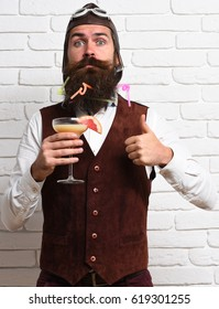 handsome bearded aviator man with long beard and mustache on surprised face holding glass of alcoholic cocktail in vintage suede leather waistcoat with hat and glasses on white brick wall background