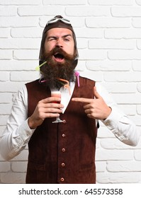 handsome bearded aviator man with long beard and mustache on funny face holding glass of alcoholic shot in vintage suede leather waistcoat with hat and glasses on white brick wall background
