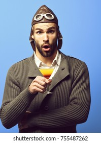 handsome bearded aviator man with long beard on surprised face holding glass of alcoholic cocktail in gray knitted sweater with hat and glasses on blue studio background