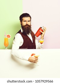 handsome bearded barman with long beard and mustache has stylish hair on serious face holding shaker and made alcoholic cocktail in vintage suede leather waistcoat on purple green studio background