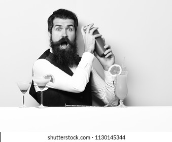 handsome bearded barman with long beard and mustache has stylish hair on surprised face holding shaker and made alcoholic cocktail in vintage suede leather waistcoat on purple green studio background.