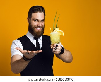 handsome bearded barman with a long beard and mustache has stylish hair offers to treat himself and try a cocktail of his cooking, he is wearing a classic waistcoat on a yellow studio background
