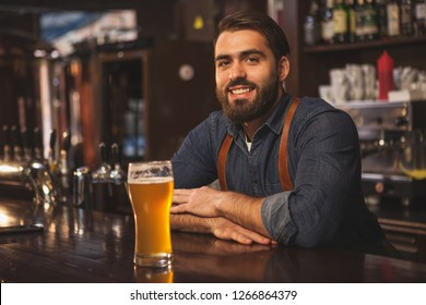 Handsome bearded bartender smiling joyfully to the camera, leaning on the bar counter, serving delicious beer at his pub, copy space. Brewer offering tasty craft beer at his restaurant