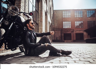 Handsome bearded biker with classic style black motorcycle. Cafe racer.