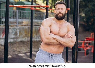 Handsome bearded bodybuilder man with perfect muscular body posing outdoors. Strong man with naked torso standing, looking away.
