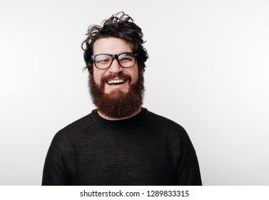 Handsome bearded boy in glasses smiles and looks at the camera