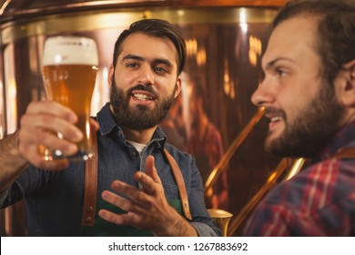 Handsome bearded brewer smiling, talking to his colleague while examining freshly brewed craft beer. Two beermakers working at microbrewery. Food and drink production, small business concept