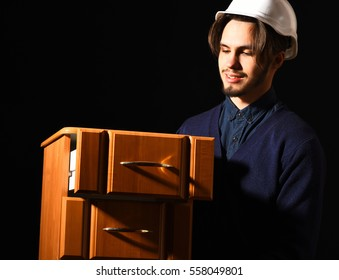 handsome bearded builder or foreman in blue sweater and helmet on smiling face holding wooden bedside on black studio background