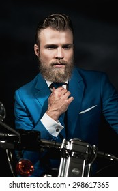 Handsome bearded businessman in a blue suit sitting waiting on a motorbike in the darkness looking thoughtfully, with copyspace