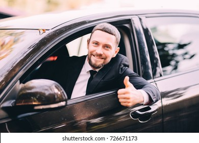 Handsome bearded businessman in a car with thumbs up