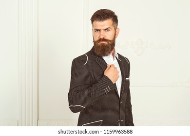 Handsome bearded businessman in classic suit is adjusting his jacket. Portrait of elegant rich confident smart with modern hairdress haircut beard creative virile dreamy luxurious pensive freelancer