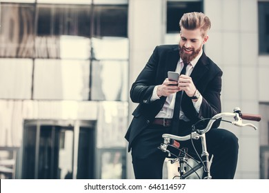 Handsome bearded businessman in classic suit is using a smart phone and smiling while riding bicycle in city