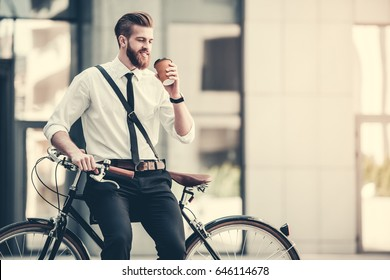 Handsome bearded businessman in classic suit and with bag is drinking coffee and smiling while riding bicycle in city