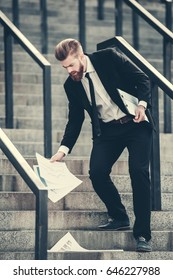 Handsome bearded businessman in classic suit is dropping documents while going down the stairs in the city center