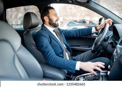 Handsome bearded businessman dressed in the suit driving a car in the city
