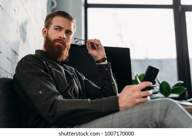 handsome bearded businessman sitting and holding glasses with smartphone