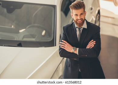 Handsome bearded businessman in suit is looking at camera and smiling while standing with crossed arms in car dealership
