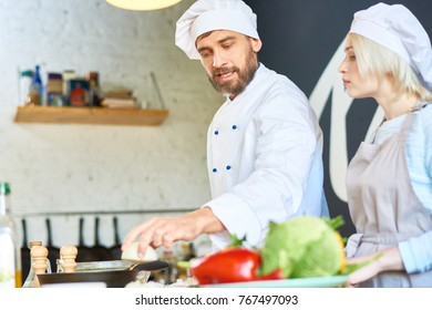 Handsome bearded chef wearing uniform explaining pretty woman how to prepare vegetable soup correctly while conducting cooking workshop at modern restaurant kitchen