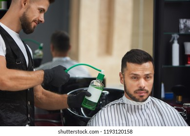 Handsome bearded client of barbershop sitting in striped coiffure cape and looking away. Male hairdresser in black gloves sprinkling special green water on haircut of client.