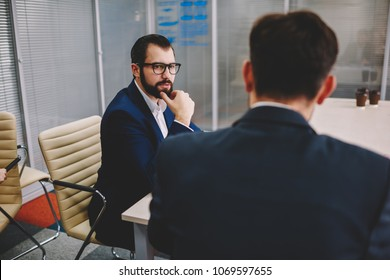 Handsome bearded entrepreneur in formal wear attentively listening business proposal from partner during meeting in office interior.Corporate director discussing productive strategy with employee