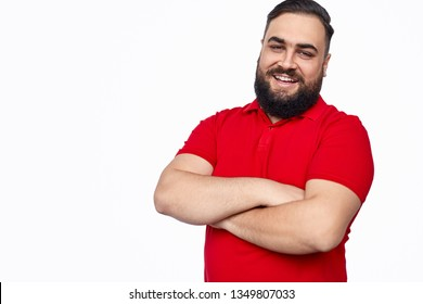Handsome bearded ethic male in red T-shirt keeping arms folded and friendly smiling while standing against white background and looking at camera
