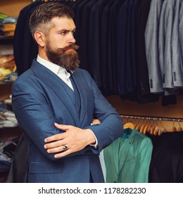 Handsome bearded fashion man in classical blue costume suit. Handsome brutal man suit, tailor in his workshop. Men with beard clothing, boutiques. Tailor, tailoring. Stylish men's suit. Amazing style