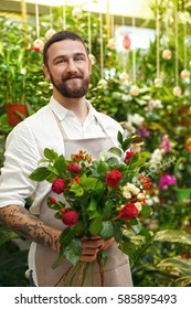 Handsome bearded florist with beautiful bouquet in greenhouse