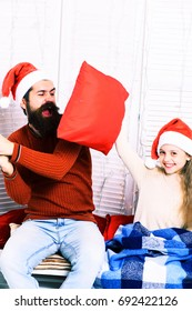 handsome bearded funny man with long beard in christmas hat and cute blonde smiling girl with blue checkered plaid fight with red pillows on white studio background