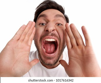 Handsome bearded funny man is yelling with his mouth opened wide is isolated on a white background with his hands up high