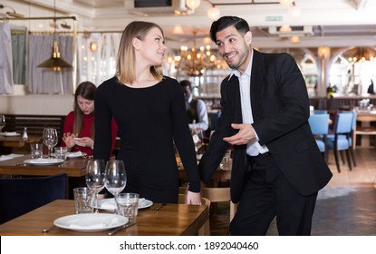Handsome bearded gentleman helping young attractive woman with her chair in restaurant.