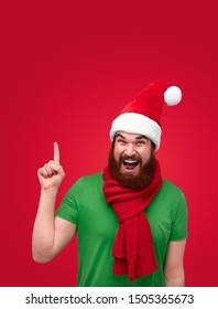 Handsome bearded guy in Christmas hat and scarf screaming and pointing up while standing on bright red background