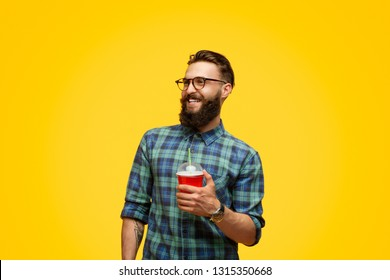 Handsome bearded guy with cup of fresh drink smiling and looking away while standing on vivid yellow background