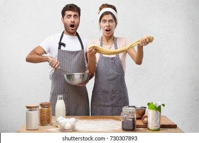 Handsome bearded guy and cute woman feeling shocked and terrified looking like a mess while baking pastry, watching online cooking recipe video step by step. Failure and disaster in kitchen