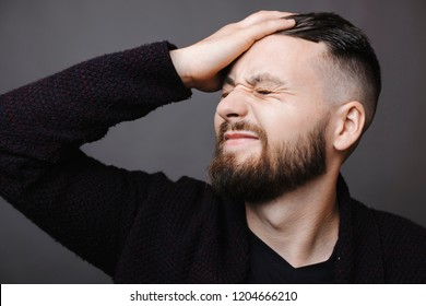 Handsome bearded guy grimacing and slapping forehead with hand while standing on gray background