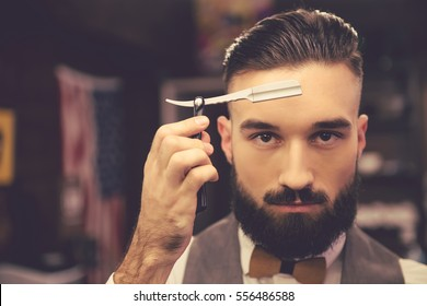 Handsome bearded hairdresser in stylish classic wear is holding a straight razor while standing at the barbershop