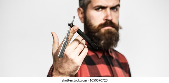Handsome bearded hairdresser in stylish wear is holding a straight razor while standing at the barbershop. Straight razor, barbershop, beard. Vintage straight shaver. Barbershop service concept.