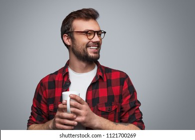 Handsome bearded hipster in checkered shirt and glasses holding white cup of coffee looking away on gray