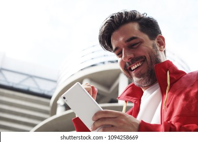 Handsome bearded hipster euphoric winner winning a betting and watching a smart phone with football stadium background. Man celebrate win a bet with a gambling mobile app. soccer bet, sports gambling.