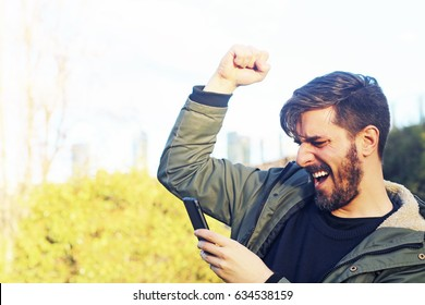 Handsome bearded hipster euphoric winner winning a bet and watching a smart phone with a city park background. Man celebrate win a bet with a gambling mobile app. Play mobile app games outdoors
