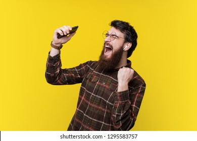 Handsome bearded hipster, excited listening music and gesturing over yellow background