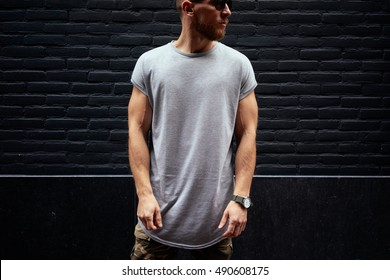 A handsome bearded hipster guy in a blank gray t-shirt is looking aside while standing on a black brick wall background. Empty place for the logo or design. Mock up.