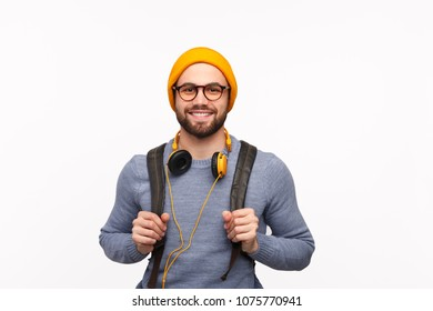Handsome bearded hipster guy in colorful hat and eyeglasses wearing backpack and headphones smiling at camera.