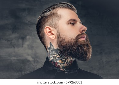 Handsome bearded hipster male with tattoo on his neck.