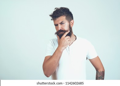 handsome bearded hipster man portrait with lush moustache and stylish hair on thoughtful face and white T-shirt touching long beard and thinking isolated. thoughtful young man standing by the wall.
