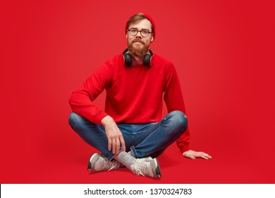 Handsome bearded hipster in red hat and sweatshirt looking at camera while sitting against red background
