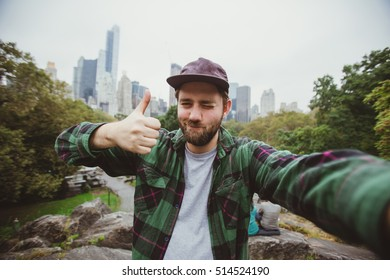 Handsome bearded hipster taking selfie with camera in Central Park, New York. Happy student makes funny picture for his blog.